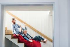 Ein erwachsener Hippie-Sohn und ein älterer Vater zuhause zu Hause, Spaß habend lizenzfreies stockbild