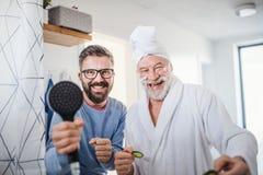 Ein erwachsener Hippie-Sohn und ein ?lterer Vater im Badezimmer zuhause zu Hause, Spa? habend stockbild