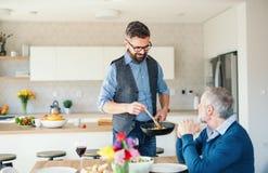 Ein erwachsener Hippie-Sohn und ein ?lterer Vater zuhause zu Hause, kochend stockbilder
