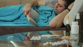 Ein erwachsener kranker Mann liegt auf dem Sofa, das hinter einer Decke sich versteckt und liest ein Buch, das in Taschenbuch ges stock video footage