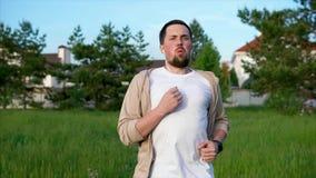 Ein erwachsener Mann, der aktiv Läufe durch den Park im Sommer zur Schau trägt stock footage