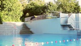 Ein erwachsener Mann, der in das Wasser springt stock footage