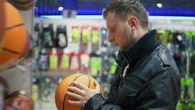 Ein erwachsener Mann in der schwarzen Lederjacke überprüft die Bälle, die auf den Regalen im Supermarkt liegen Ein Mann betrachte stock footage
