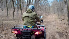 Ein erwachsener Mann in der Tarnungskleidung und in einem Schutzhelm auf seinem Kopf fährt um den Wald auf ein reifendes Viererka stock video
