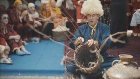 Ein erwachsener Mann in einem nationalen Kostüm spinnt einen Korb Ein alter Moslem spinnt einen Korb von Zweigen Nationalfeiertag stock video footage