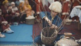 Ein erwachsener Mann in einem nationalen Kostüm spinnt einen Korb Ein alter Moslem spinnt einen Korb von Zweigen Nationalfeiertag stock video