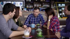 Ein erwachsener Mann mit dem kurzen Haar, gekleidet in einem karierten Hemd, erklärt seinen Freunden, das mit ihm an einem Holzti stock footage