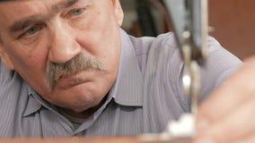 Ein erwachsener Mann mit einem Schnurrbart näht auf einer alten hand-genähten Maschine stock video
