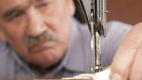 Ein erwachsener Mann mit einem Schnurrbart näht auf einer alten hand-genähten Maschine stock footage
