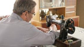 Ein erwachsener Mann mit einem Schnurrbart näht auf einer alten hand-genähten Maschine Gläser werden gekleidet und weißer Stoff w stock footage