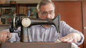 Ein erwachsener Mann mit einem Schnurrbart näht auf einer alten hand-genähten Maschine Gläser werden gekleidet und weißer Stoff w stock video footage