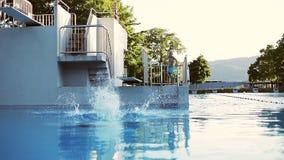 Ein erwachsener Mann taucht in das Pool im Sommer stock video footage