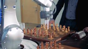 Ein erwachsener Mann und ein robotized Arm spielen Schach und bewegliche Stücke stock video