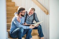 Ein erwachsener Sohn und ein älterer Vater, die zuhause auf Treppe zu Hause, Fotografien betrachtend sitzt stockfotos