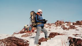 Ein Erwachsener und ein erfahrener Bergsteiger im Lager mit seinem Team ist am Rand eines schneebedeckten Hügels und überprüft stock video