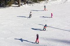 Ein Erwachsener und vier Kinder, die guten Schnee genießen Stockbild
