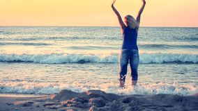 Ein erwachsenes Mädchen des schwarzen Schattenbildes steht nahe dem Rand von Meer und von Ausdehnungen, stock footage