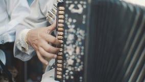 Ein Erwachsenmann spielt ein Akkordeon in einem nationalen Kostüm Musikalisches Quartettspielen Musiker führen am Konzert durch E stock footage