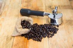 Ein Espressomaschinengruppenanführer und Kaffeebohnen in den Säcken Stockfotografie