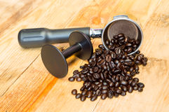 Ein Espressomaschinengruppenanführer und Kaffeebohnen mit tampe Stockfotografie