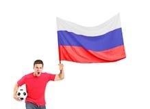 Ein euphorisches Gebläse, das eine Kugel und eine russische Markierungsfahne anhält Lizenzfreies Stockfoto