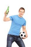 Ein euphorisches Gebläse, das ein Bierflasche- und Fußballzujubeln anhält Stockfotos