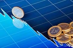 Ein-Euro-Münzen auf Abwärtstendenzdiagramm. Stockfotos