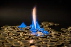 Ein-Euro-Münzen auf Feuer Stockbilder