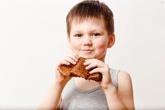 Ein fünfjähriger russischer Junge in einem grauen T-Shirt isst einen Ölpfannkuchen auf einem weißen Hintergrund Maslenitsa lizenzfreie stockfotografie