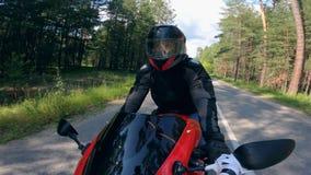 Ein Fahrer im Sturzhelm, der ein Motorrad auf eine Straße reitet stock video