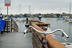Ein Fahrrad auf einem Dock, das heraus über dem Newport-Hafen in Richtung zu einigen Segelbooten Liegeplatz betrachtet lizenzfreies stockfoto