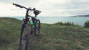 Ein Fahrrad steht auf einem grünen Rasen der Seeküste mit Blick auf das Gebirgszugkonzept der aktiven Erholung und der gesunden l stockbild