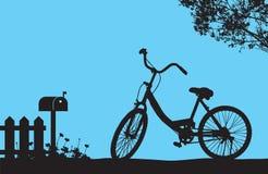 Ein Fahrradparken unter blühendem Blumenbaum nahe hölzernem Zaun und Briefkasten, Blumenwiese aus den Grund Stockfoto