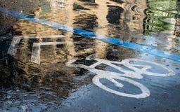 Ein Fahrradsymbol auf den Straßen in der regnenden Zeit Lizenzfreies Stockbild