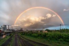 Ein farbiger Regenbogen über der metallurgischen Anlage Lizenzfreie Stockfotografie