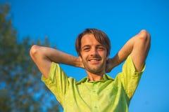 Ein Farbporträtfoto eines glücklichen lächelnden behaarten Mannes des Brunette, der ein Gelbgrünhemd gegen ein blauer Himmel back Stockfoto
