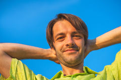 Ein Farbporträtfoto eines glücklichen lächelnden behaarten Mannes des Brunette, der ein Gelbgrünhemd gegen ein blauer Himmel back Stockfotos