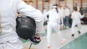 Ein fechtendes Turnier in der Halle Junge Mädchen, die auf ihre Drehung hält einen Sturzhelm stehen und warten stock video footage