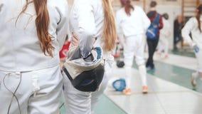 Ein fechtendes Turnier in der Halle Junge Mädchen, die auf ihre Drehung stehen und warten stock footage