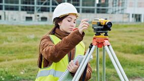 Ein Feldmesser der jungen Frau in der Arbeitskleidung und -sturzhelm justiert die Ausrüstung und produziert Berechnungen auf dem  stock footage