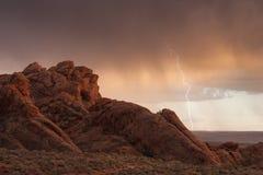 Ein Felsgelände in roten Cliff Desert Reserve in Süd-Utah dient als Vordergrund für einen Sommerbeleuchtungssturm Stockfotos