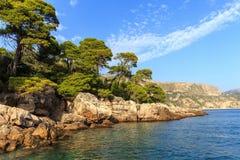 Ein felsiges Ufer, Boote und ein Schiff kroatien Sonniger Tag Stockfotografie