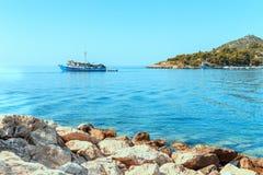 Ein felsiges Ufer, Boote und ein Schiff Lizenzfreie Stockfotos
