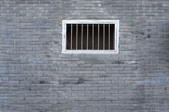 Ein Fenster auf der grauen Backsteinmauerhintergrundbeschaffenheit Stockbild