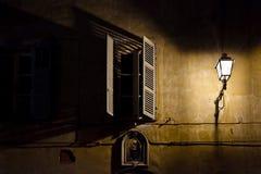 Ein Fenster in der Dunkelheit nahe einem hellen Pfosten Lizenzfreie Stockfotografie
