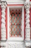 Ein Fenster in einem Gitter zwischen zwei symmetrischen Spalten Stockbild