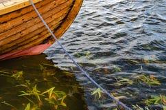 Ein festgemachtes hölzernes Boot mit Meerespflanze im Wasser lizenzfreie stockfotografie