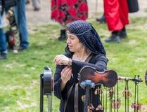 Ein Festivalteilnehmer, der im Kostüm einer mittelalterlichen Dame gekleidet wird, versucht an ein künstliches Armband am Purim-F lizenzfreie stockfotos