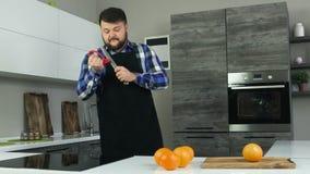 Ein fetter bärtiger Mann in einem Schutzblech steht in der Küche und schärft ein Messer vor der Tabelle mit Orangen Ein großer Ma stock video