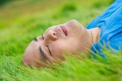 Fetter Mann, der auf dem grünen Gras liegt, um sich zu entspannen Stockbild